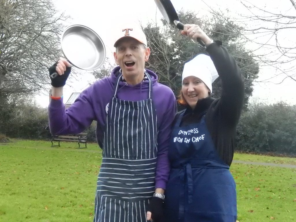 Pancake day race competitors hold frying pans in the air.