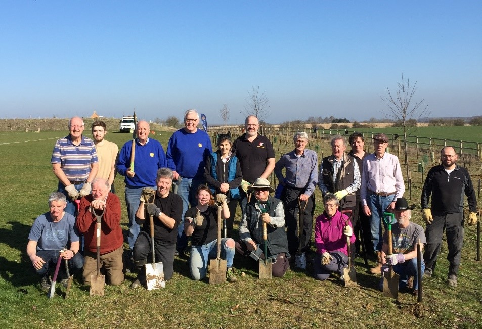 Volunteers gathered together after planting trees at Lace Hill on a sunny day