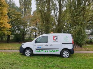Image of the electric van parked in an autumnal Bourton Park.