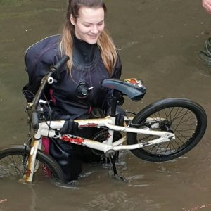 Woman in the river holding a found bike at the river rinse