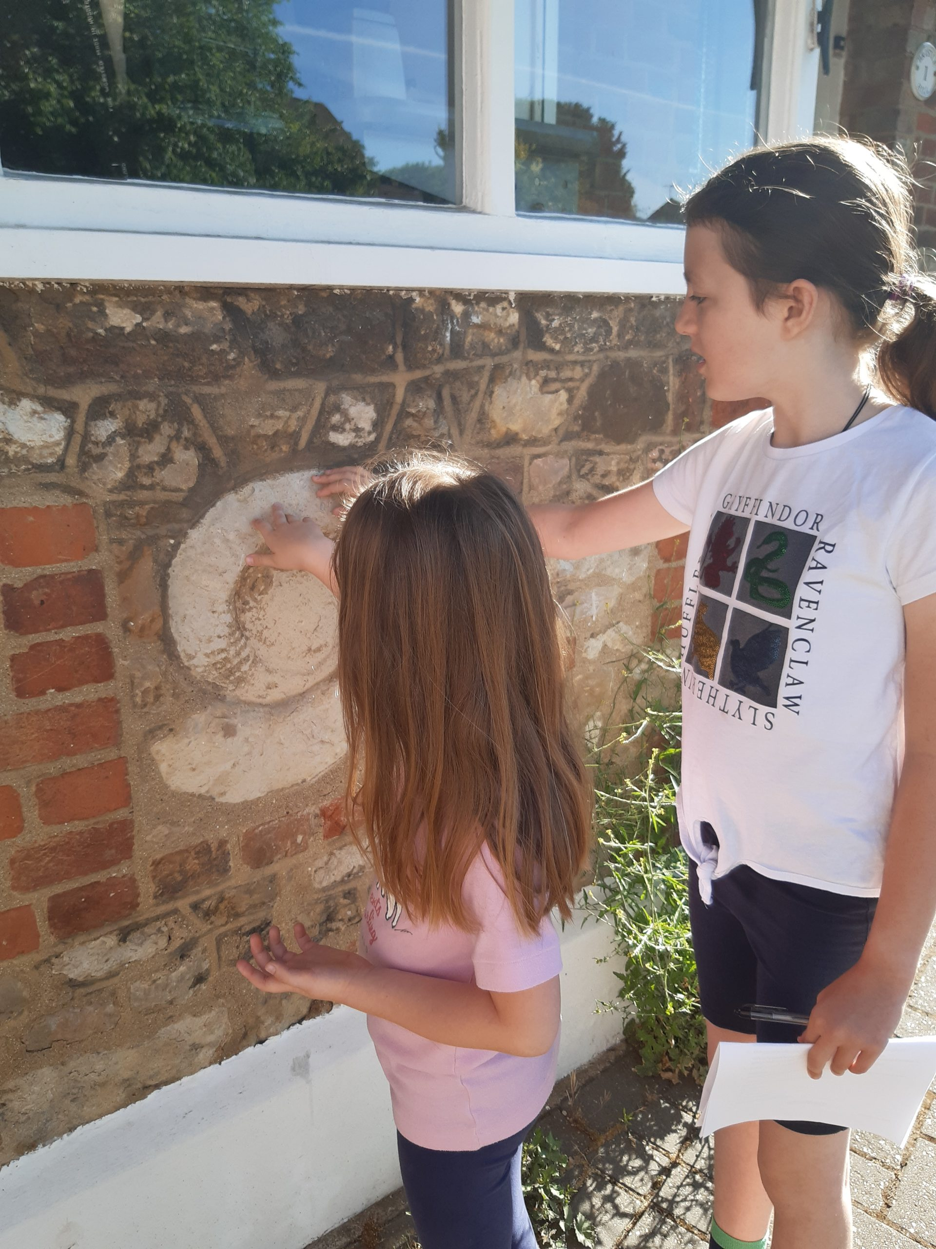 Two children touch ammonite set into a brick wall