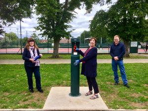 The Mayor is stood in Chandos Park, filling her water bottle from the new fountain. She is flanked (at a distance) by two other Councillors.