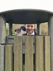 Boy looking through bin and dropping litter into the bin.