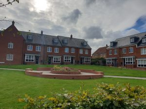 Communal Brick Circular Area Surrounded By Houses and A Green
