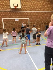 Children learn a dance routine in a sports hall