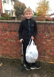 Boy posing with litter picker and bag of rubbish