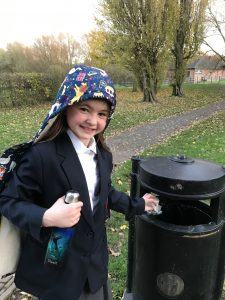 Young girl in uniform throwing litter into a park bin