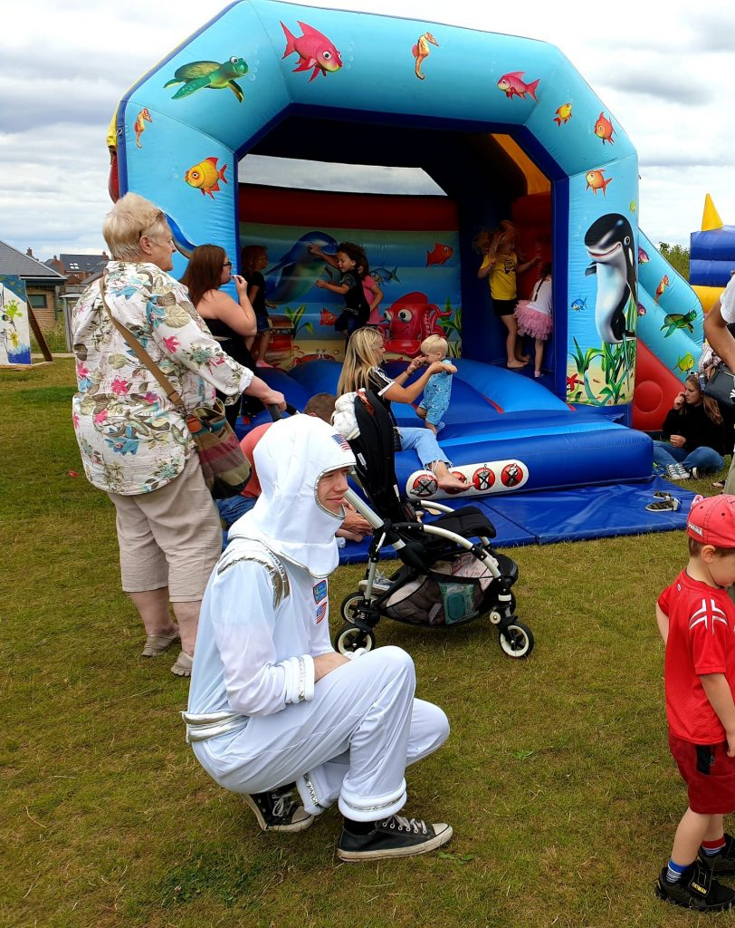 families play around a bouncy castle