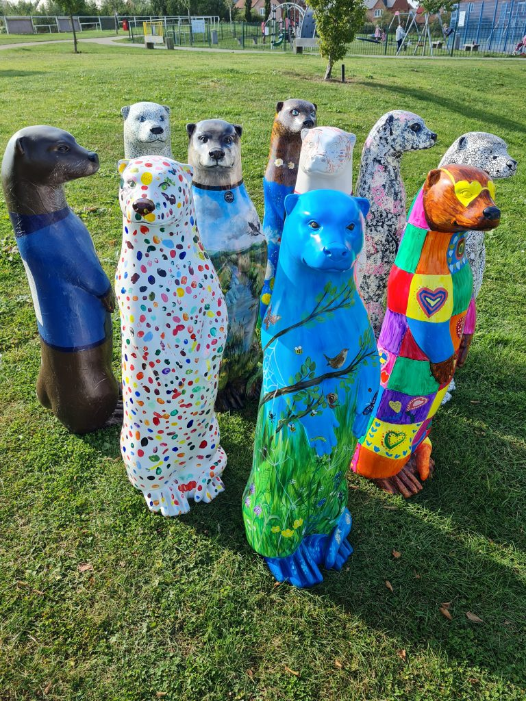 Photograph of painted otter sculptures